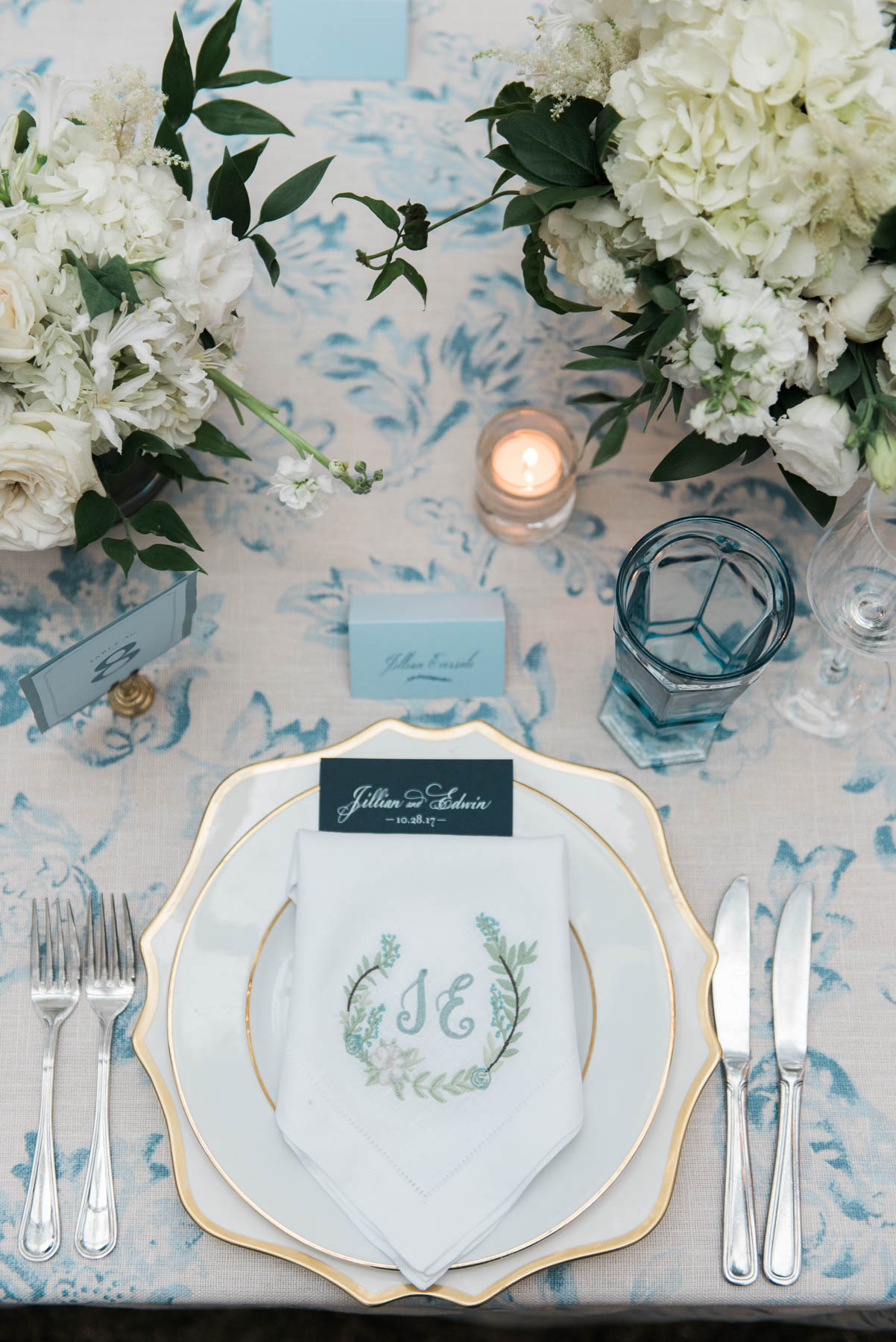A monogrammed napkin at the bride's seat on her wedding day with a blue and white tablescape // Rhyme & Reason