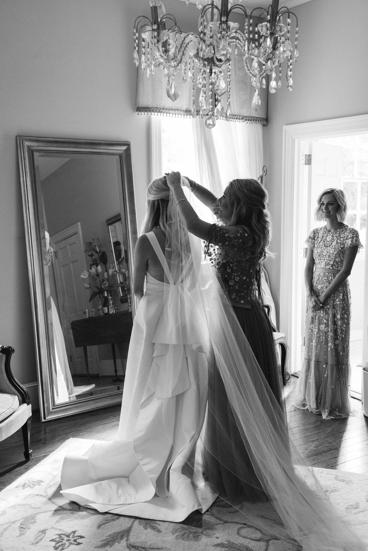 Bridesmaids helping the bride put on her veil for her Charleston wedding day // Rhyme & Reason